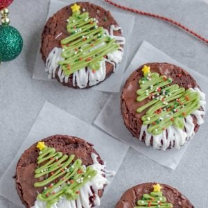 An overhead picture of 2 Christmas Brownies with Christmas ornaments and ribbon surrounding them.