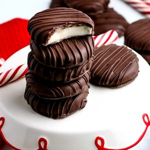 Five peppermint patties stacked on top of each other with a bite taken out of one.