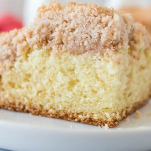 A close up picture of a slice of crumb cake on a white plate.