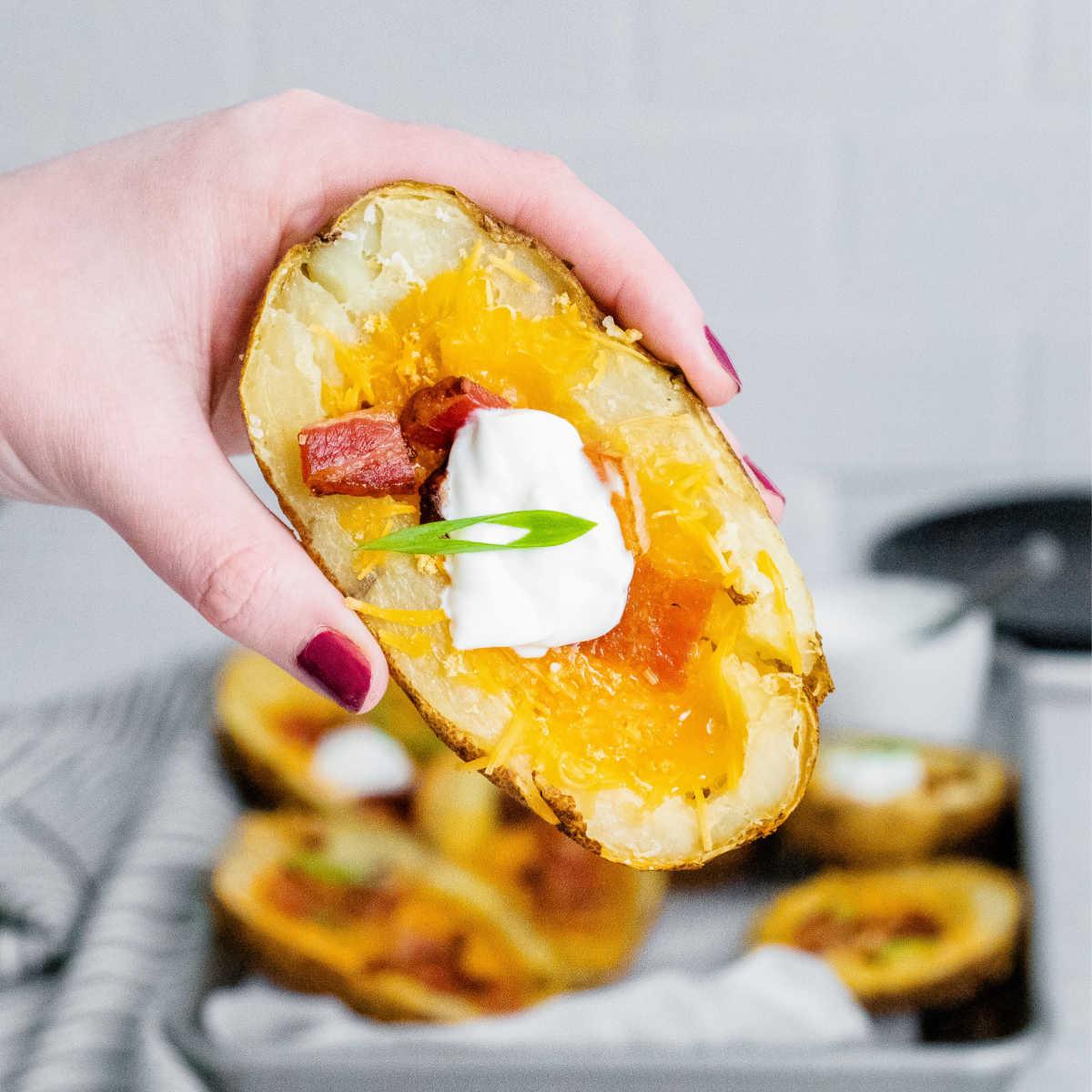 A hand holding a potato skin.