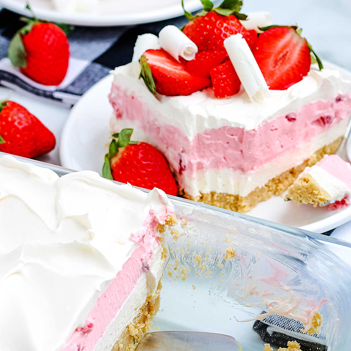 A piece of Strawberry Cheesecake Lasagna on a plate and the rest in the pan.