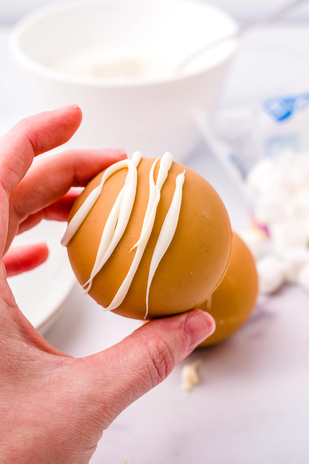 A hand holding a finished Peanut Butter White Hot Chocolate Bomb.