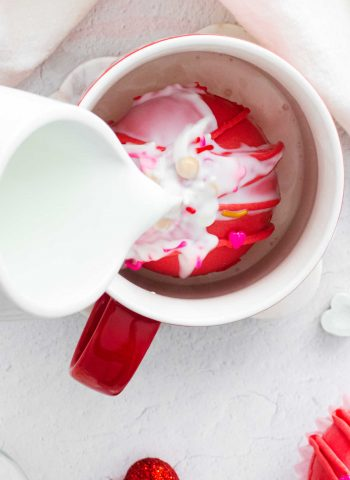 Warm milk being poured onto a Red Velvet Hot Chocolate Bomb.
