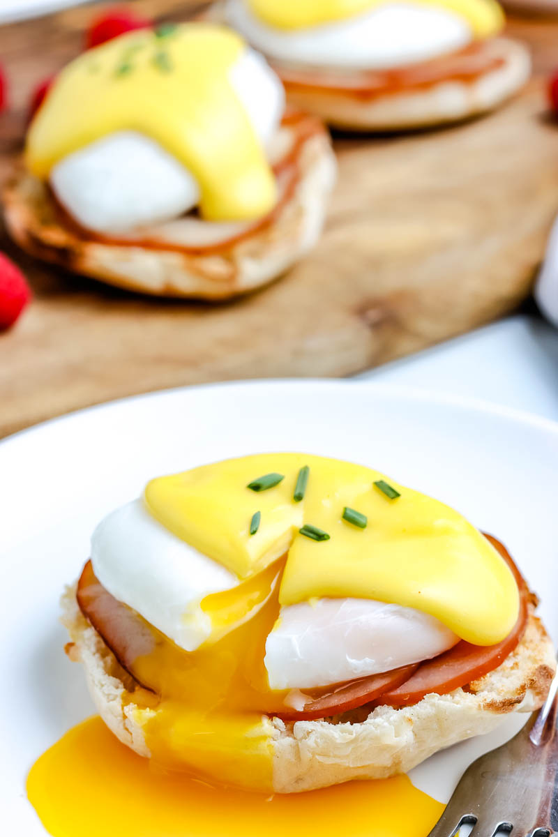 Eggs Benedict on a white plate with the yolk running out.