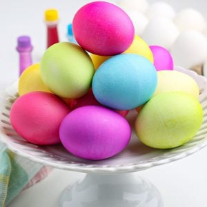 How to Dye Easter Eggs with Food Coloring. The finished eggs are on a white cake pedestal.