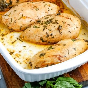 The finished Oven baked chicken breasts in a white pan.