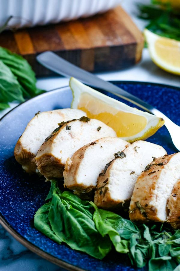 Oven Baked Chicken Breasts sliced on a blue platter.