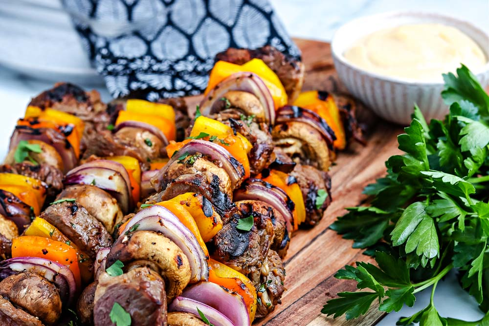 Beef Kabobs on a wooden cutting board.