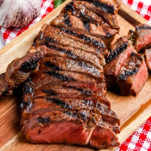 A close up picture of grilled strip steak cut into slices on a cutting board.