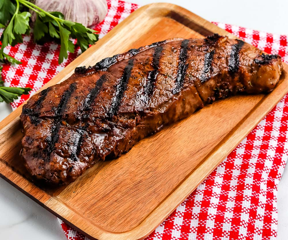 A finished Grilled New York Strip Steak on a wooden cutting board.