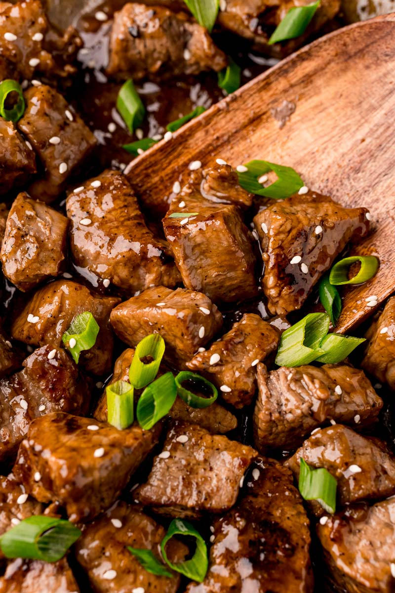 An overhead, close up picture of the finished Teriyaki Steak Tips garnished with sesame seeds and green onions.