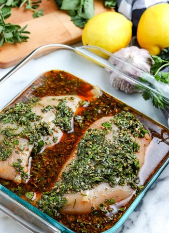 Two chicken breasts sitting in a dish of marinade.