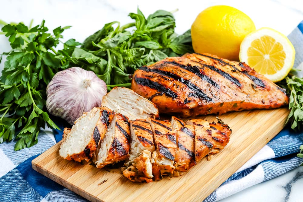 The finished Grilled Chicken Breasts on a wooden cutting board.