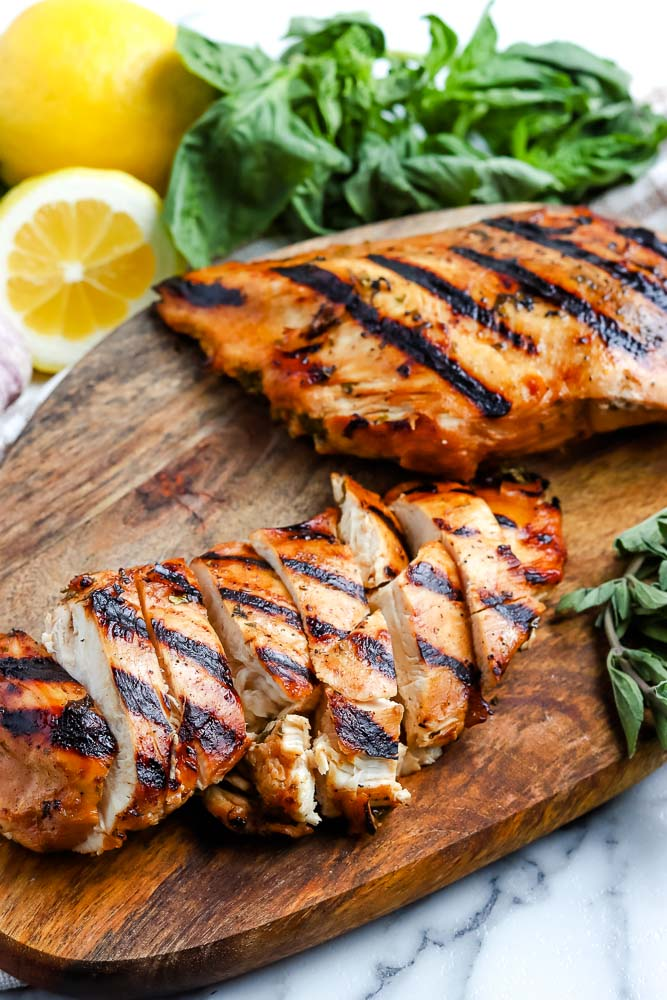 A close up picture of the finished grilled chicken on a wooden cutting board.