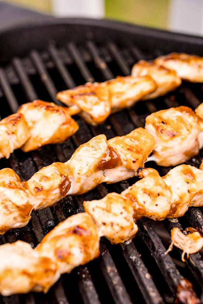 Chicken skewers cooking on a grill.
