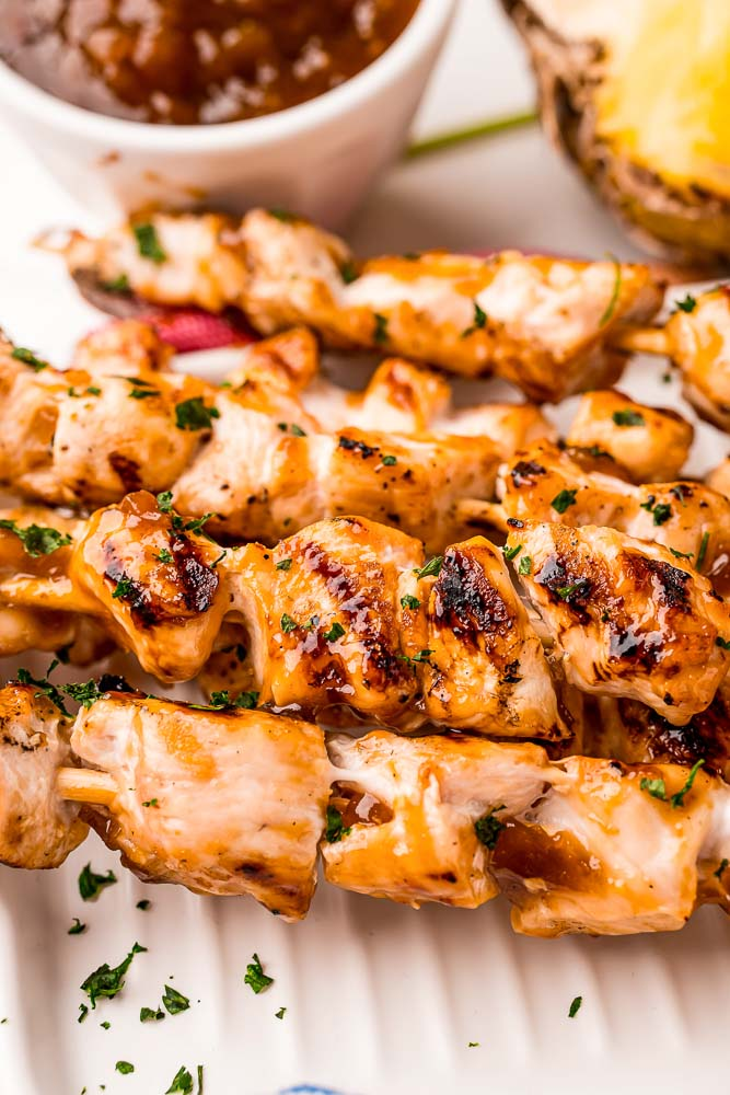 A close up picture of a pile of Grilled Chicken Skewers on a white platter.