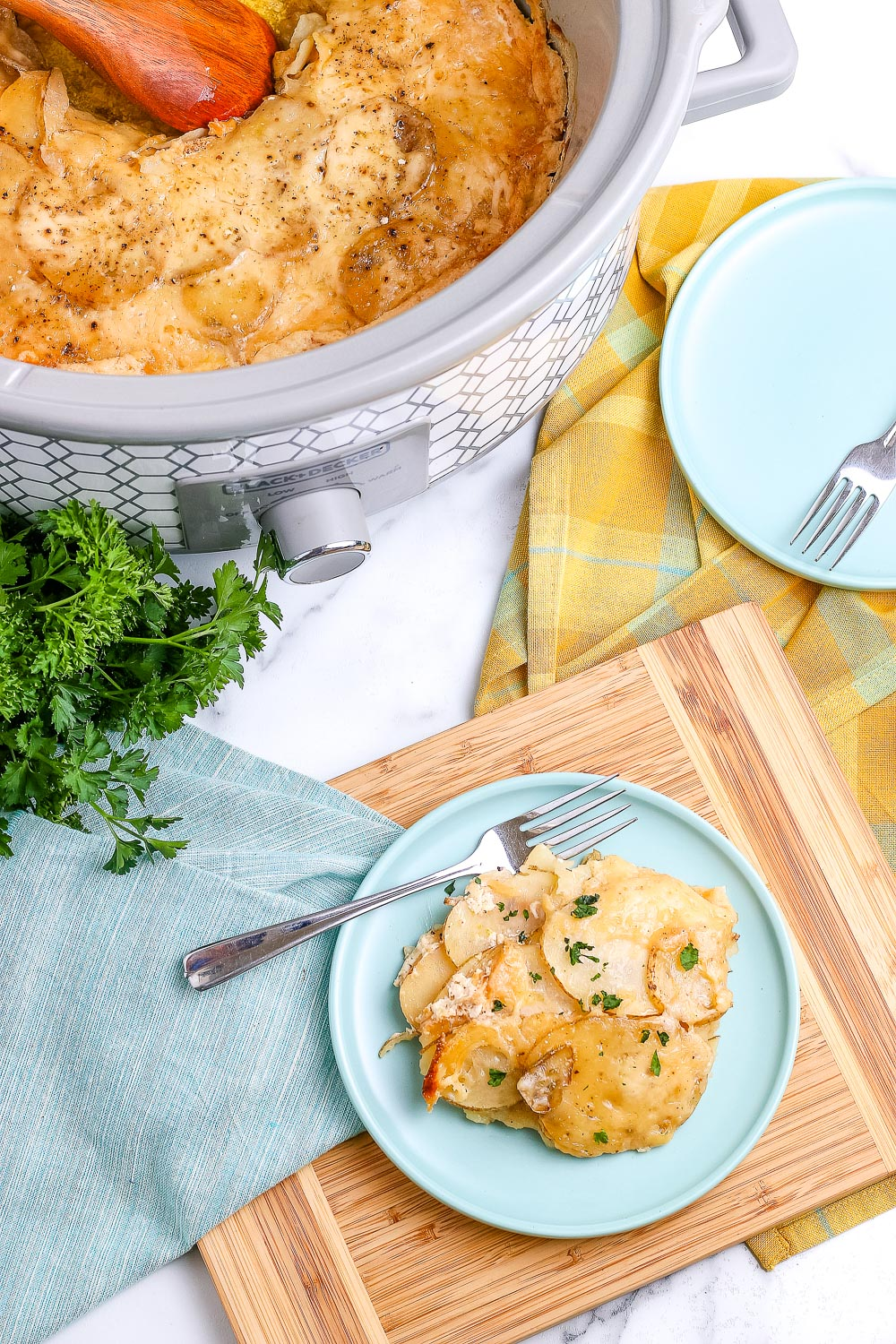 An overhead picture of scalloped potatoes on a plate and in a crockpot.