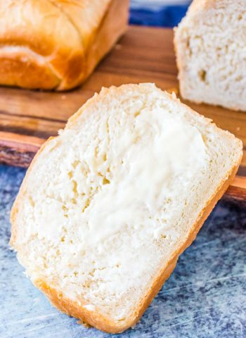 A slice of farmhouse white bread with butter on it.
