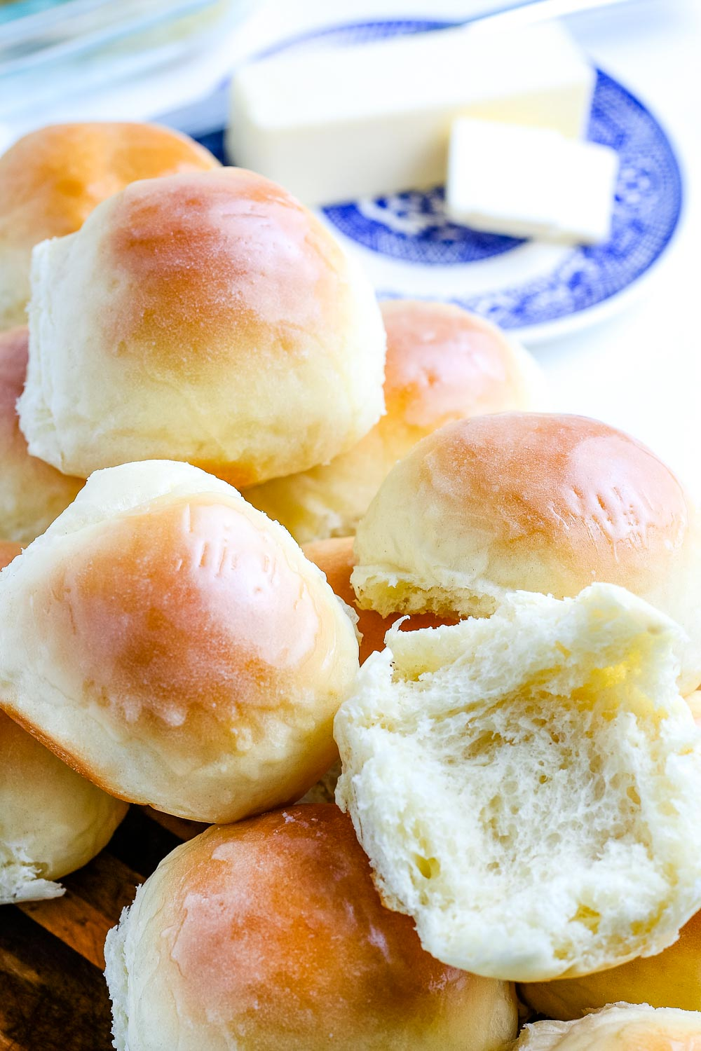 A stack of Homemade Dinner Rolls and butter in the background.