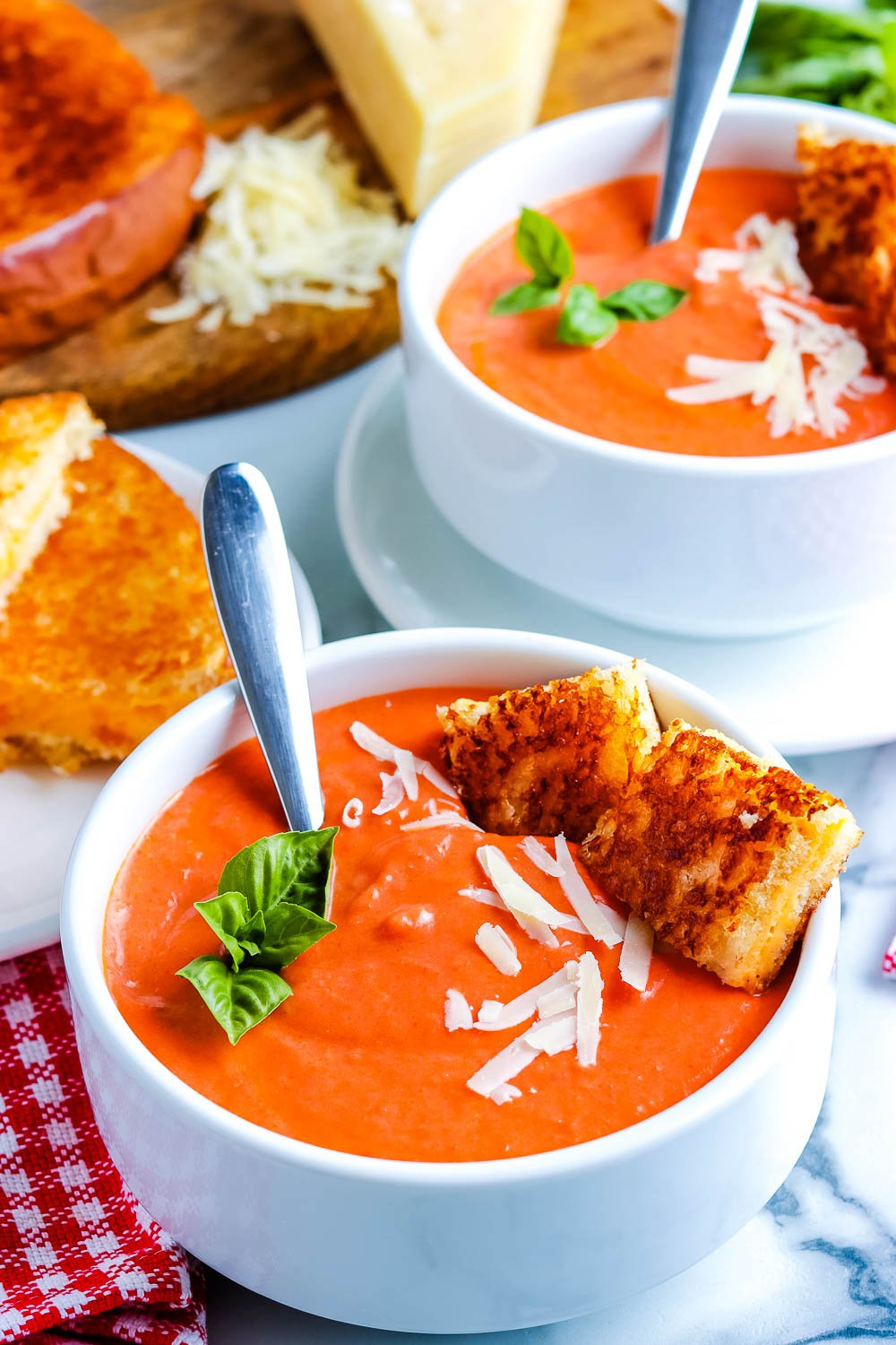 Tomato Soup in white bowls garnished with small grilled cheese cubes and basil.