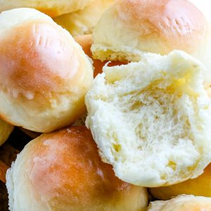A close up picture of Homemade Dinner Rolls and one cut in half so you can see how soft and fluffy they are.