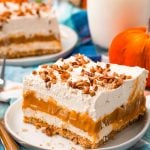 A close up picture of pumpkin delight on a white plate and a fork nearby.