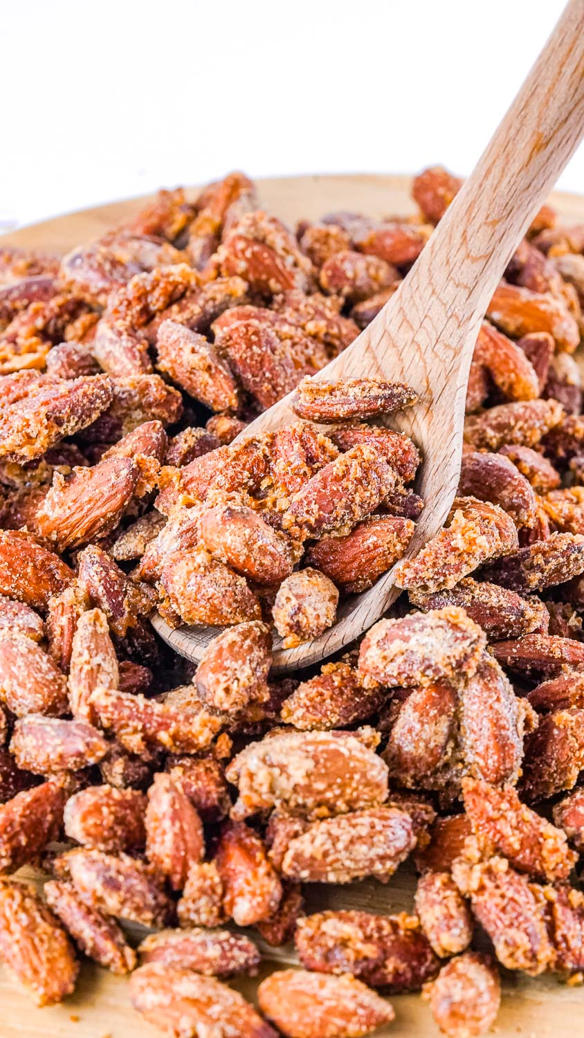 A wooden spoon picking up some of the finished Cinnamon Sugar Smoked Almonds.