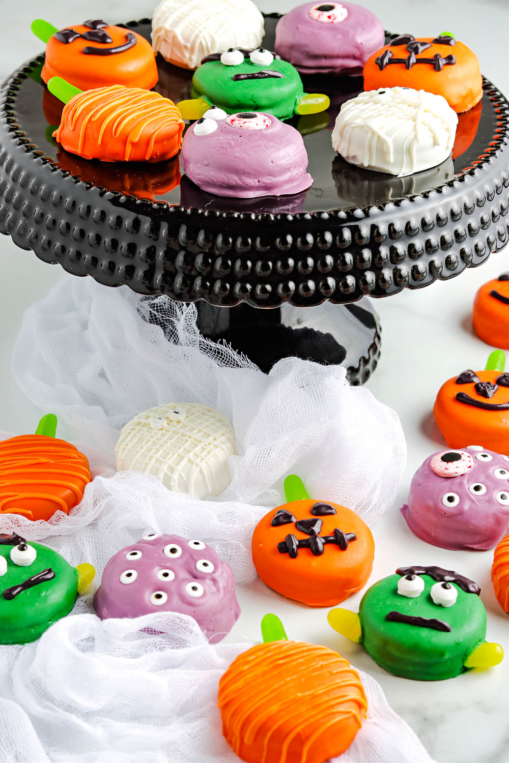 Chocolate dipped Oreos decorated for Halloween on a black cake stand and marble counter top.