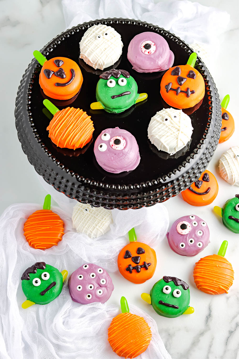 An overhead picture of finished Halloween Chocolate Dipped Oreos on a black cake stand.