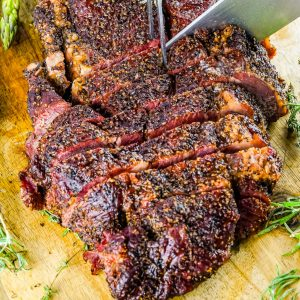 A close up picture of a smoked chuck roast being cut into.